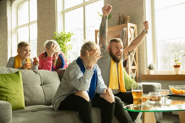 Familie juichen en tv kijken thuis in de woonkamer