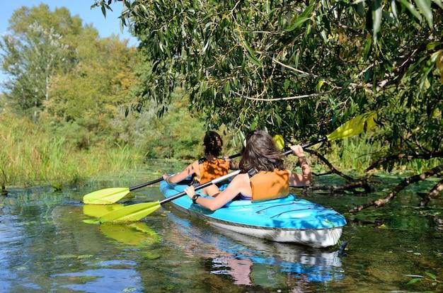 Familie kajakken, moeder en dochter peddelen in kajak op rivier kanotocht plezier, actief herfstweekend en vakantie met kinderen, fitness concept