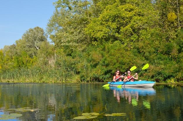Familie kajakken, moeder en kind peddelen in kajak op rivier kanotocht, actief zomerweekend en vakantie, sport en fitness concept