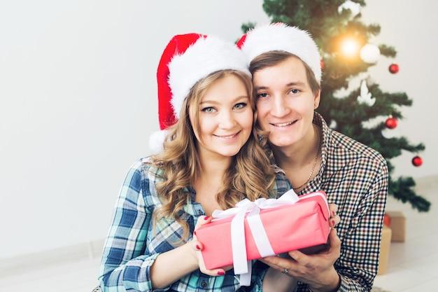 Familie, kerst, wintervakantie en mensen concept - gelukkig paar knuffelen in de buurt van kerstboom thuis.