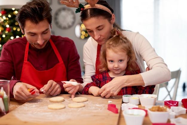 Familie kerstkoekjes in de keuken versieren