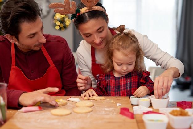 Familie kerstkoekjes samen in de keuken versieren