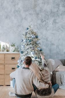 Familie kerstmis. achteraanzicht van paar zittend op de vloer omarmen, dennenboom kijken ze ingericht
