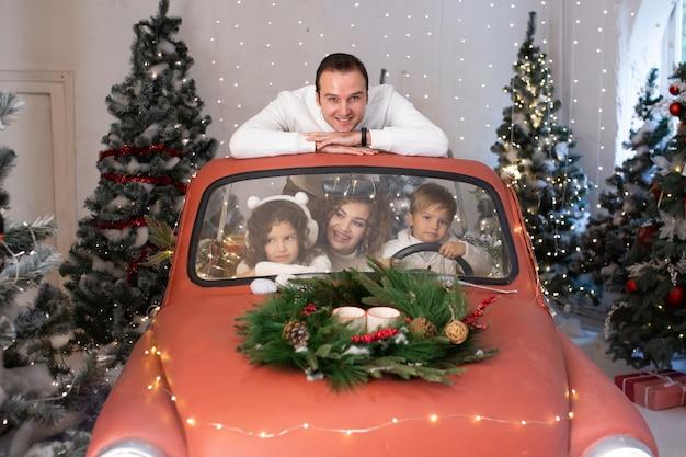 Familie kerstmis. gelukkige ouders en hun schattige dochter en zoon wachten op kerstmis