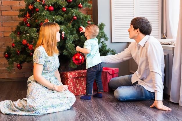 Familie, kerstmis, kerstmis, winter, geluk en mensenconcept - glimlachende familie die kerstmisboom verfraaien.