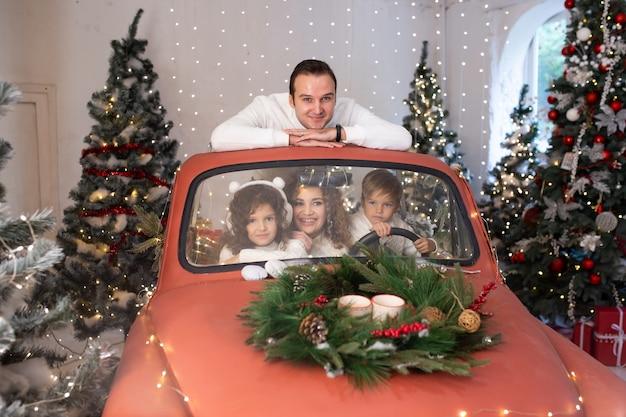 Familie kerstmis. vrolijke ouders en hun schattige dochter en zoon wachten op kerstmis