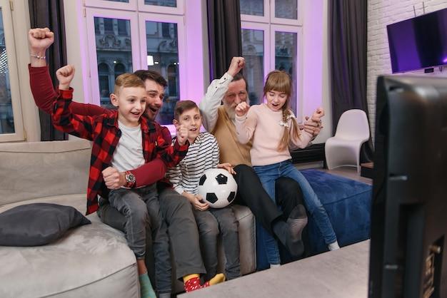 Familie kijken naar amerikaanse voetbalwedstrijd, kampioenschap op de bank thuis. fans emotioneel gejuich voor favoriete nationale ploeg. kinderen met vader en opa genieten van vrije tijd thuis.