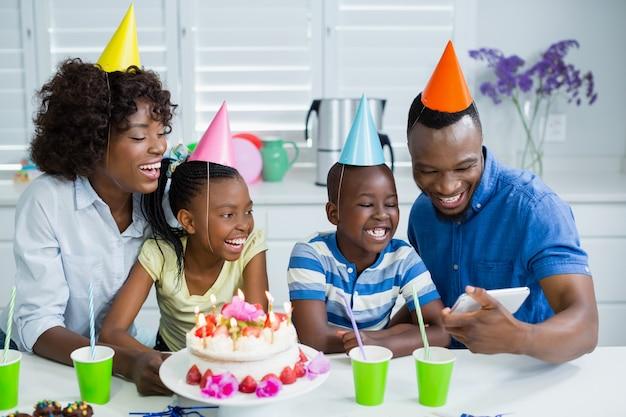 Familie kijken naar foto tijdens het vieren van verjaardagsfeestje