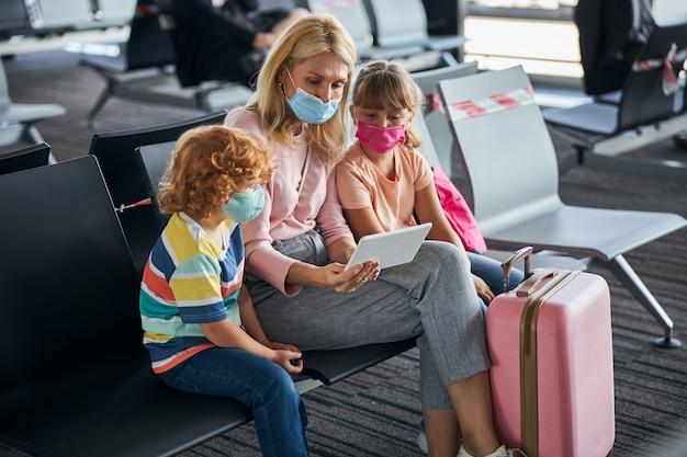 Familie kijken naar iets op een tablet op de luchthaven