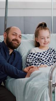 Familie kijken naar tekenfilm op televisie in ziekenhuisafdeling tijdens het wachten op medische ziekte-expertise tijdens gezondheidsonderzoek. zieke kindpatiënt die in bed rust na medicijnoperatie