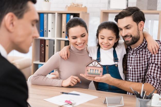 Familie kijkt naar miniatuur speelgoed huis in het kantoor van makelaar.