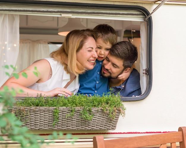 Familie kijkt uit het raam van een caravan