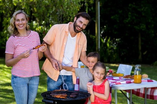 Familie kokend voedsel op barbecuegrill bij werf