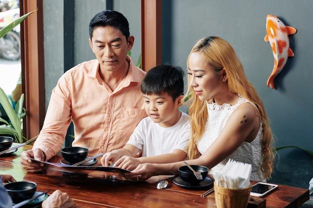 Familie leesmenu aan cafétafel