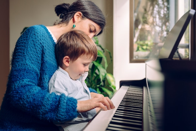 Familie levensstijl tijd samen doorbrengen binnenshuis. kinderen met muzikale deugd en artistieke nieuwsgierigheid. mamma die haar zoon thuis pianolessen onderwijzen.