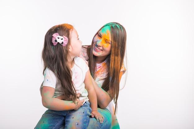 Familie, liefde en plezier concept - jonge vrouw met dochtertje lachend samen, vuil in kleuren op festival van holi