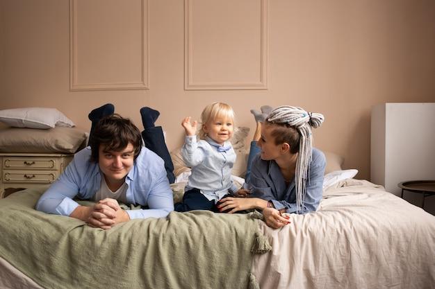 Familie liggend op bed. moeder, vader en kind met plezier in de slaapkamer. mensen die thuis ontspannen.