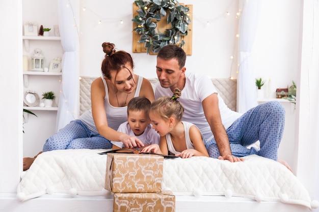 Familie liggend op bed. wintervakantie xmas en nieuwjaar concept