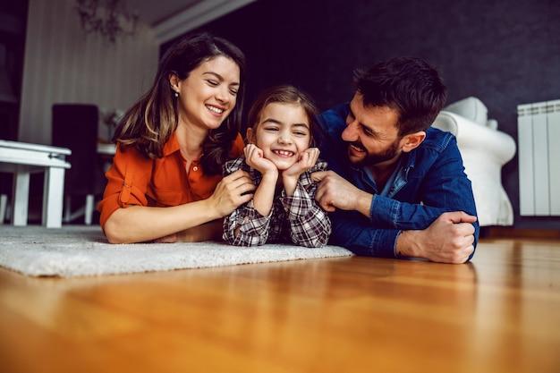 Familie liggend op de buik op de vloer. geliefde dochter lacht terwijl ouders haar veel liefde tonen.