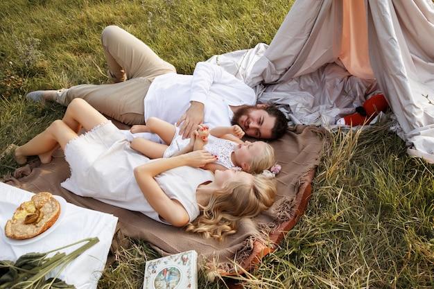 Familie ligt op het gras op een zomerpicknick. moeder vader dochter