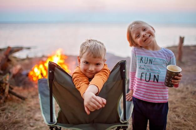 Familie lokaal uitje. kind zittend op de toeristische fauteuil en kijken naar vuur voordat 's nachts op de camping, gezonde, actieve levensstijl, veilige zomer, verblijf locatie concept