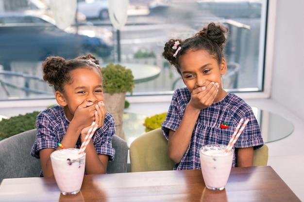 Familie-look. twee gekrulde donkerharige broers en zussen met geweldige familie kijken hardop lachen met plezier
