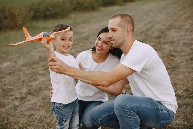 Familie loopt in een veld en speelt met speelgoedvliegtuig