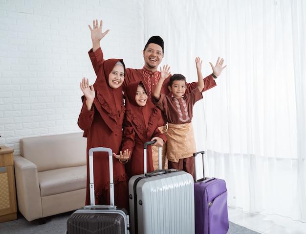 Familie met afscheid handen omhoog met koffers klaar om te mudik