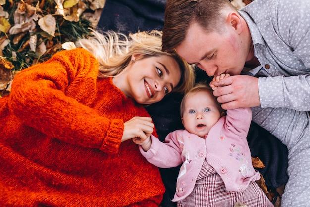 Familie met baby daugher die op bladeren in park ligt