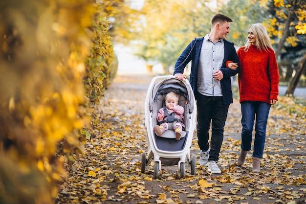Familie met baby dochter die in een de herfstpark loopt