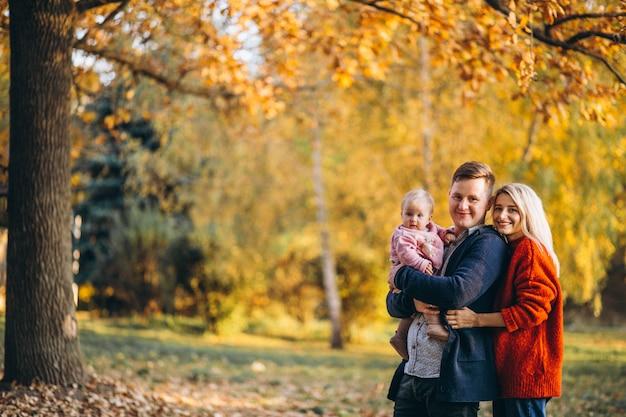 Familie met babydochter die in een de herfstpark loopt
