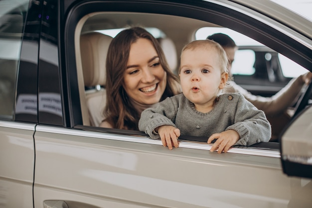 Familie met bbay girl die een auto kiest in een autosalon