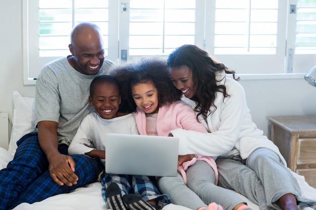 Familie met behulp van laptop op bed