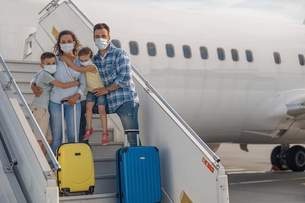 Familie met beschermende maskers, ouders met twee kleine kinderen die op de luchttrap staan, aan boord van het vliegtuig tijdens de covid19-pandemie. mensen, reizen, vakantieconcept