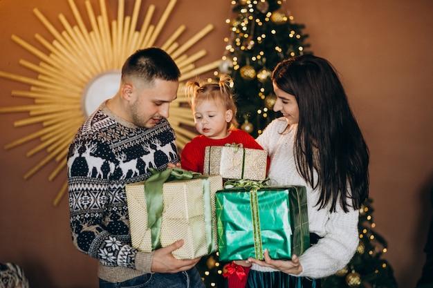 Familie met dochtertje door kerstboom uitpakken geschenkdoos