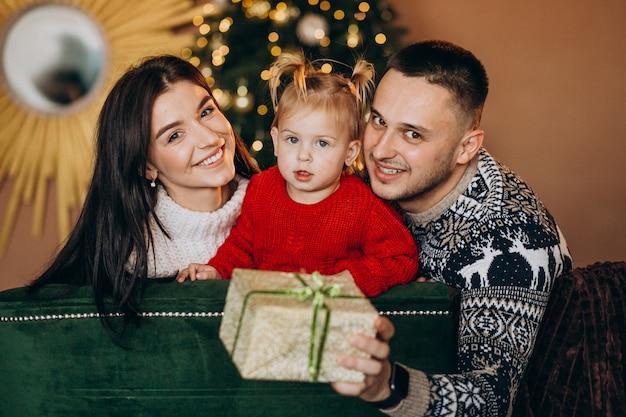 Familie met dochtertje zitten door kerstboom en geschenkdoos uitpakken