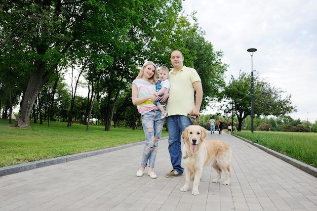 Familie met een gouden retrieverhond bij het park