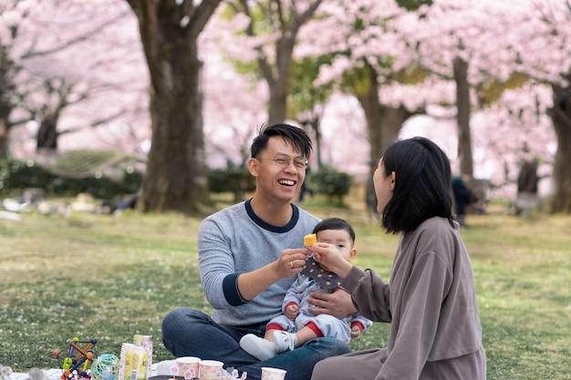 Familie met een picknick naast een kersenboom