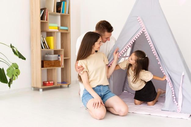 Familie met een tent in hun woonkamer