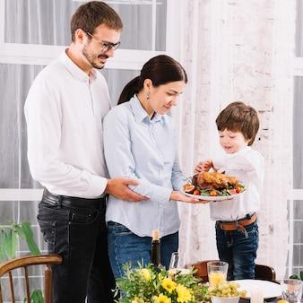 Familie met gebakken kip aan tafel
