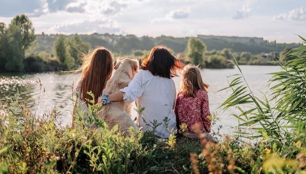 Familie met golden retriever-hond die buiten zit in de natuur