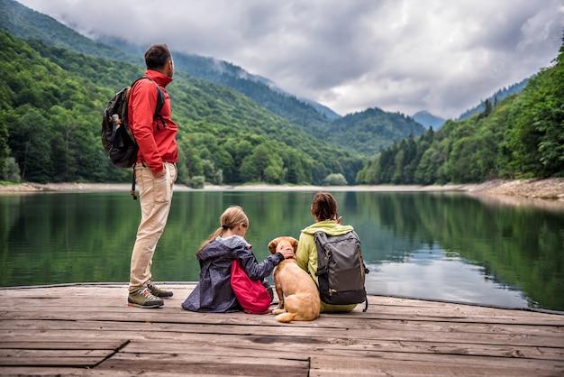 Familie met hond die op een pijler rust
