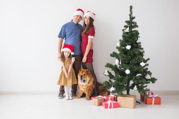 Familie met hond staan dichtbij kerstboom