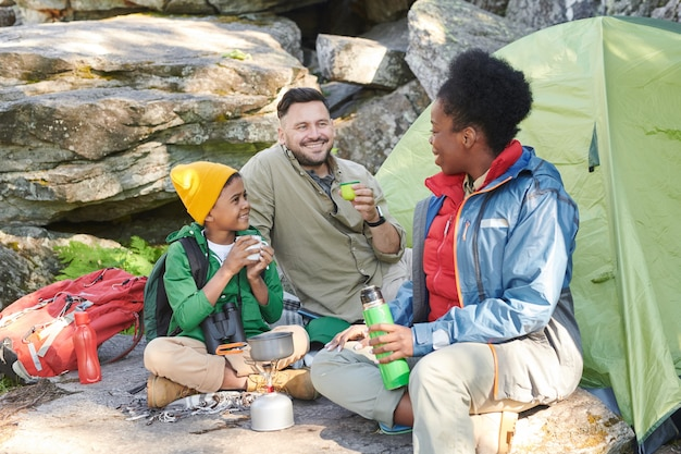 Familie met hun zoon die in de natuur met elkaar zitten praten en hete thee drinken tijdens hun reis