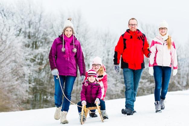 Familie met kinderen die de winterwandeling in sneeuw hebben