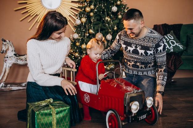 Familie met kleine dochter met kerstcadeau door kerstboom