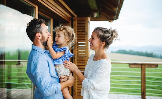 Familie met kleine dochter staande op terras van houten hut, vakantie in de natuur concept.