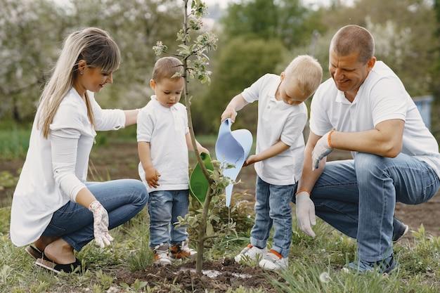 Familie met kleine zonen plant een boom op een erf