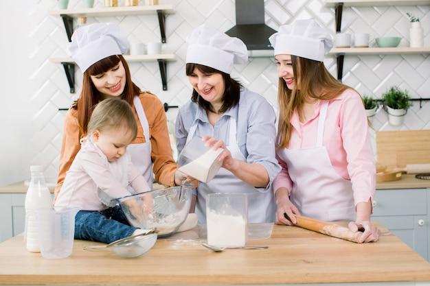 Familie met oma, twee dochters en kleine meisje bakken in de keuken. oma voegt suiker toe aan het deeg. moederdag concept, familie bakken