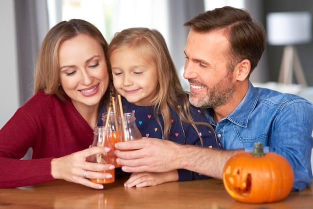 Familie met pompoen smoothie die een toost op halloween maakt